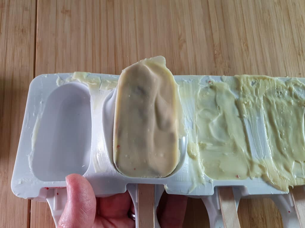 Carefully popping popsicle cakes out of molds.