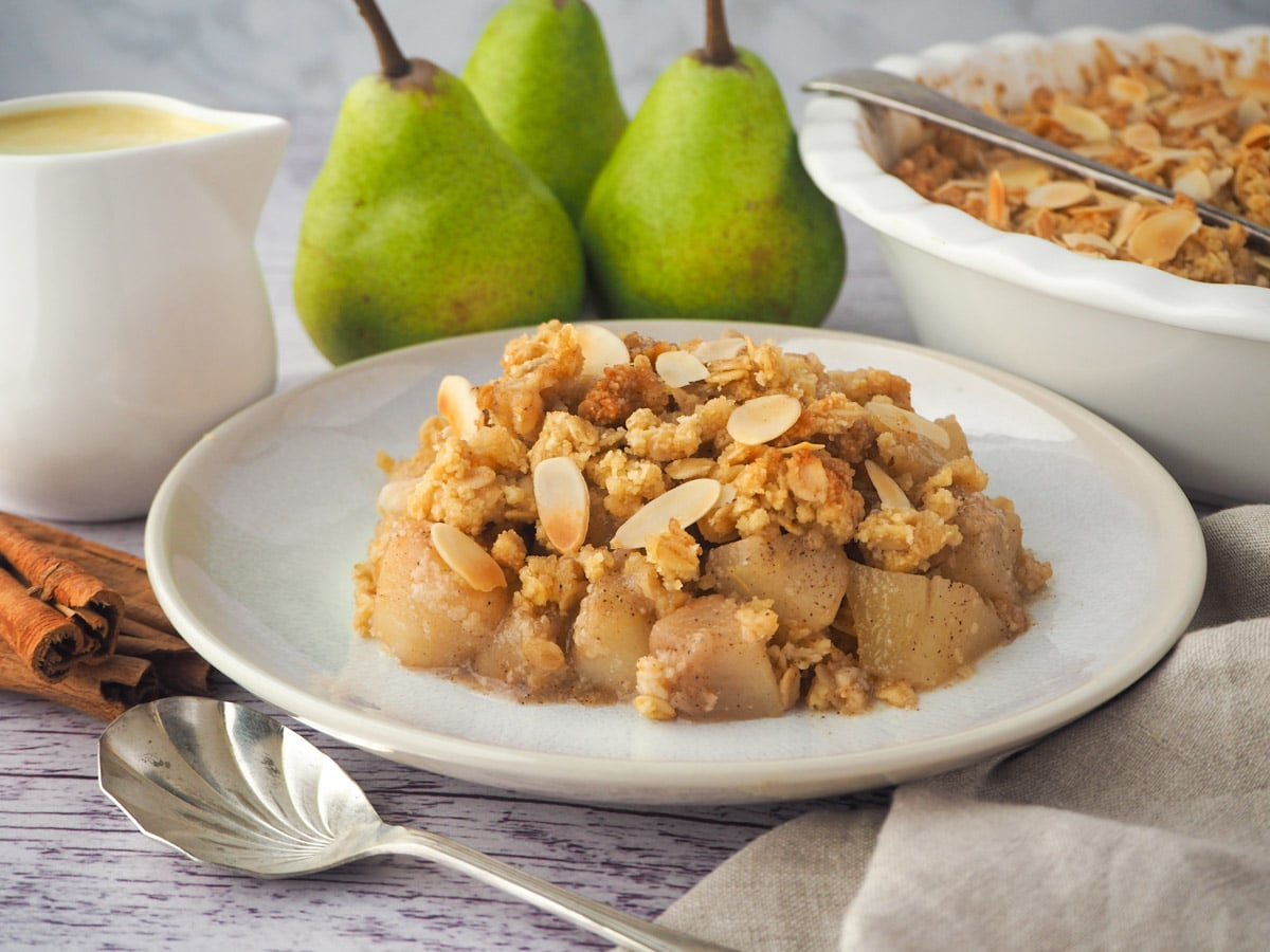 Serving of pear crumble with spoon, fresh pears, cinnamon sticks, jug of custard and baking dish of crumble in the background,