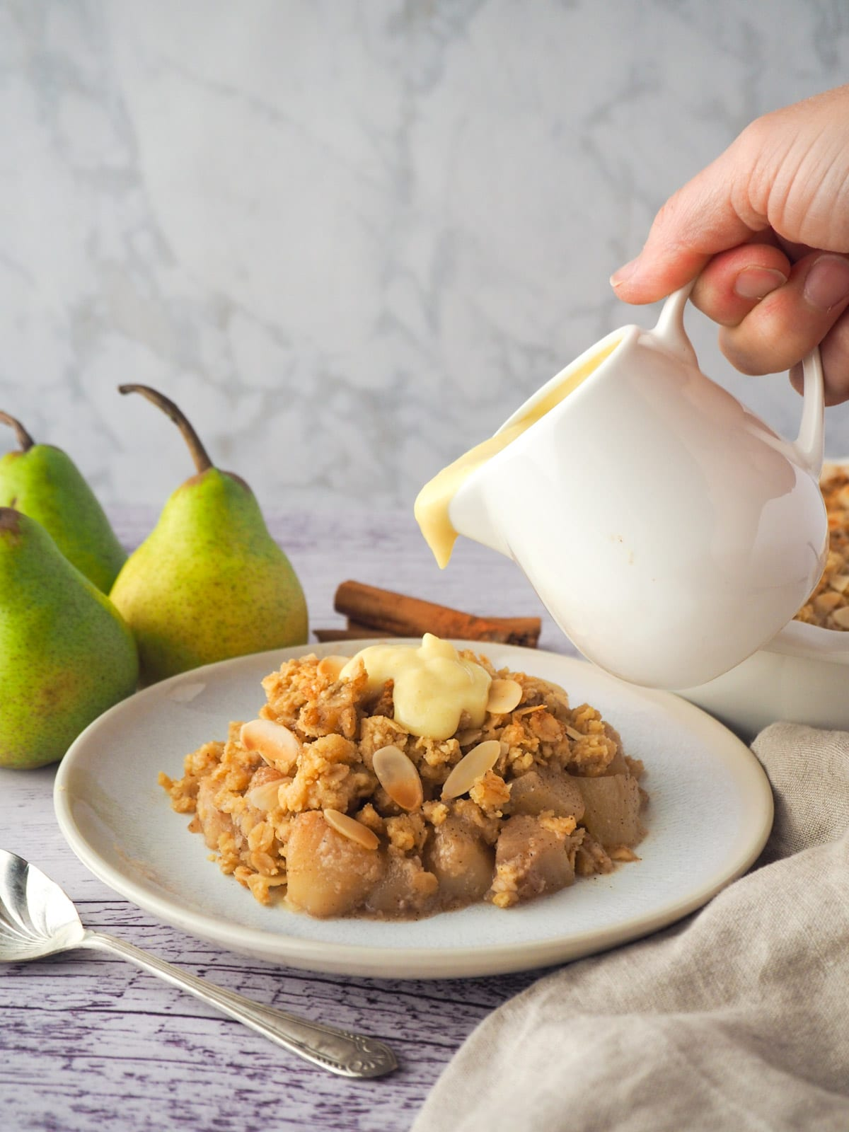 Serving of pear crumble with custard being poured over the top, with fresh pears, cinnamon stick and crumble in baking dish in background.