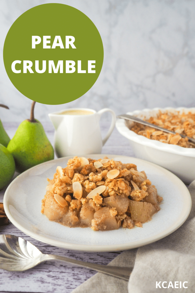 Serving of pear crumble with spoon, fresh pears, jug of custard and baking dish of crumble in the background, with text overlay, pear crumble and KCAEIC.