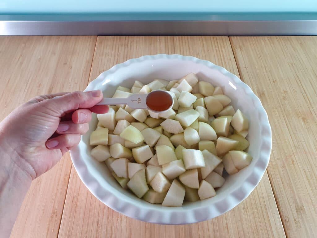 Adding vanilla extract to pears.