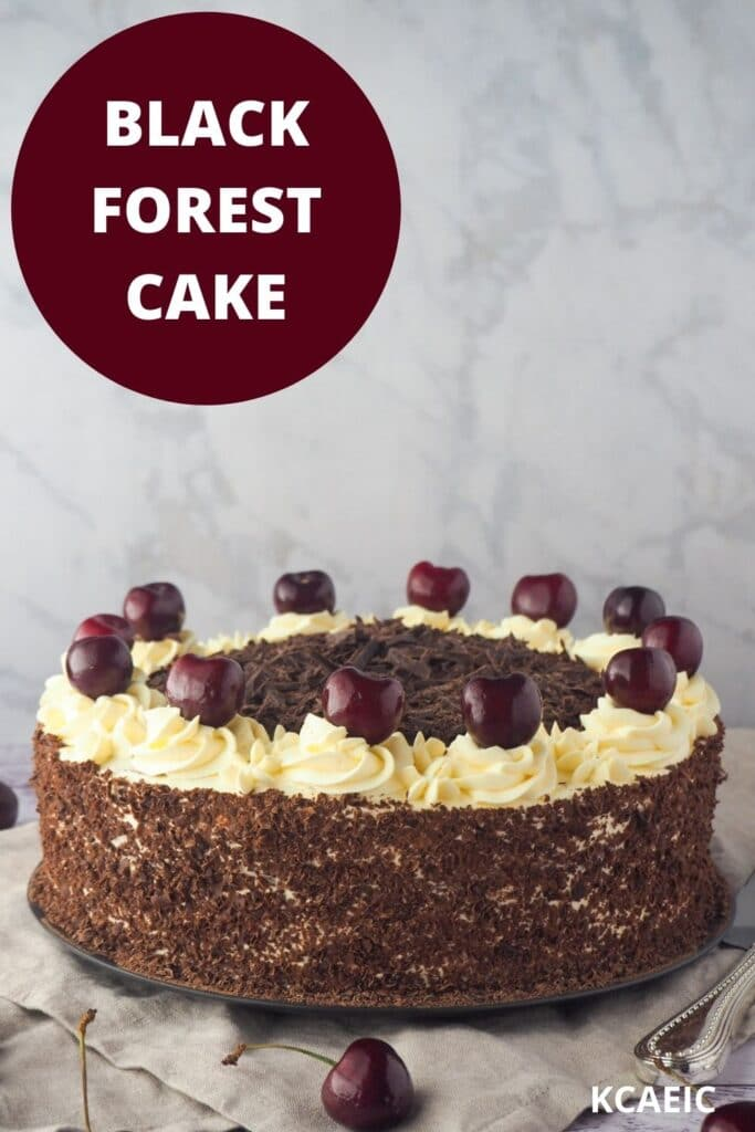 Cake with fresh cherries and silver serving utensils, with text overlay, black forest cake and KCAEIC.