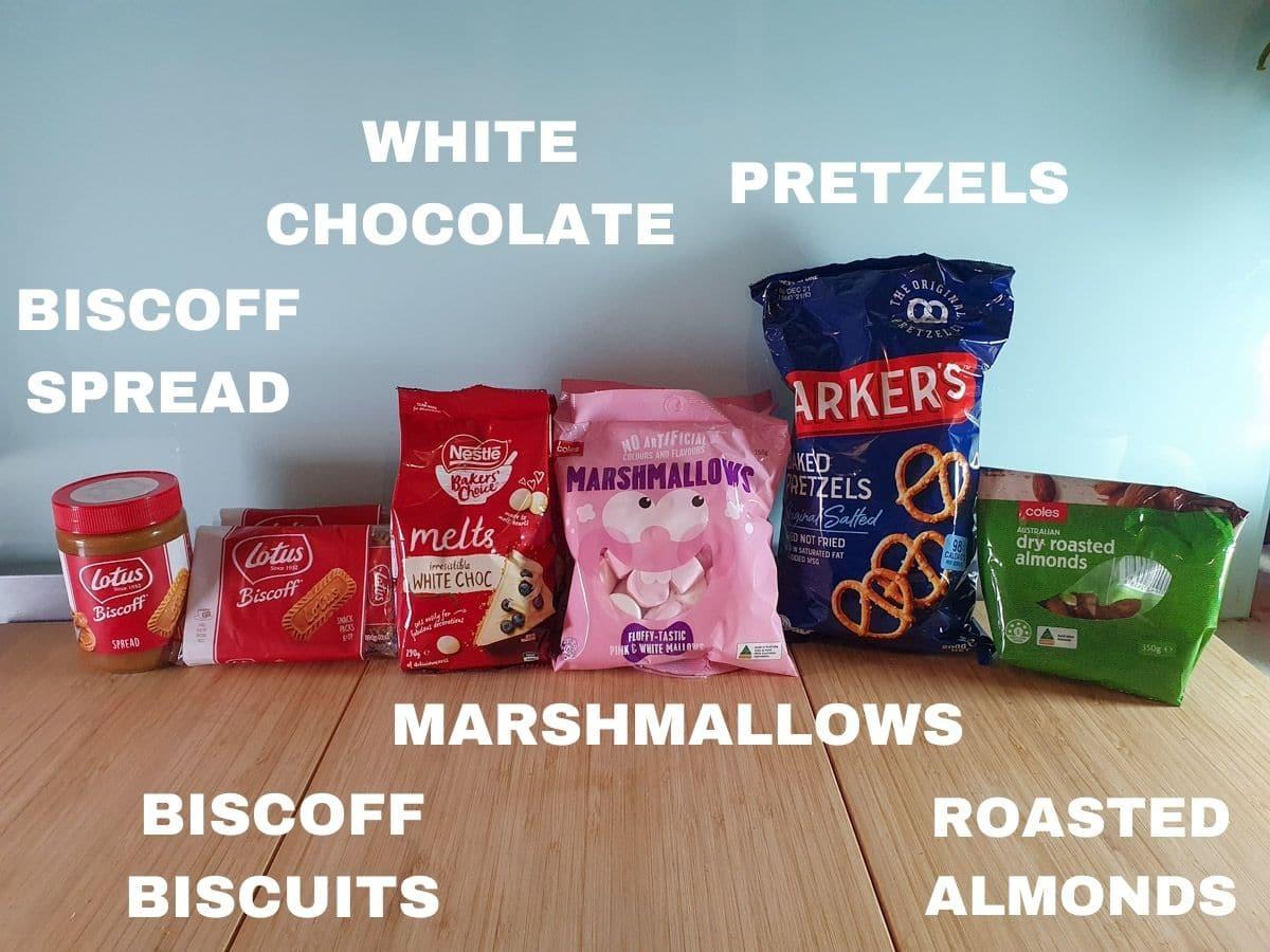ingredients, smooth biscoff spread, biscoff biscuits, white chocolate, marshmallows, pretzels, roasted almonds.