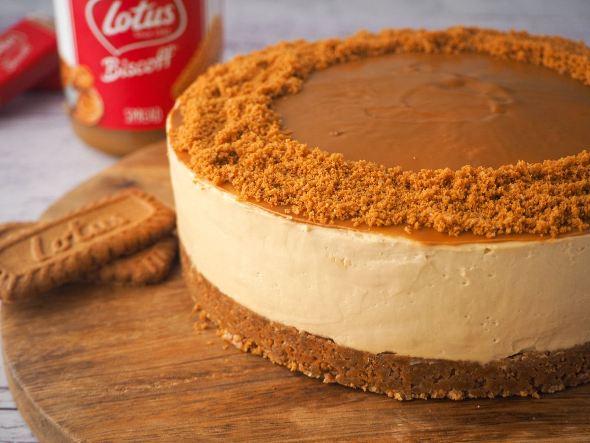 Cheesecake on a serving board with jar of Biscoff and Biscoff cookies in background.