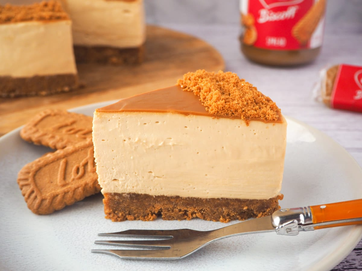 Slice of cheesecake on a plate with fork and Biscoff biscuits, with rest of cake, jar of Biscoff and Biscoff biscuits in the background.