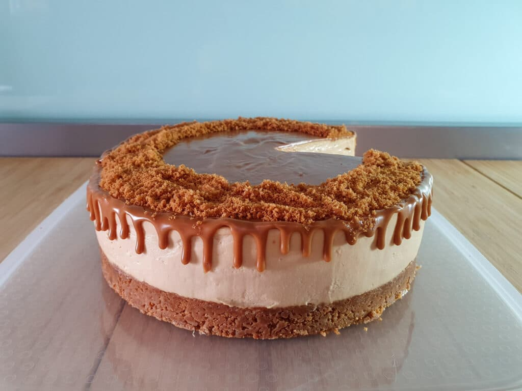 Adding biscoff spread drip to sides of cheesecake.