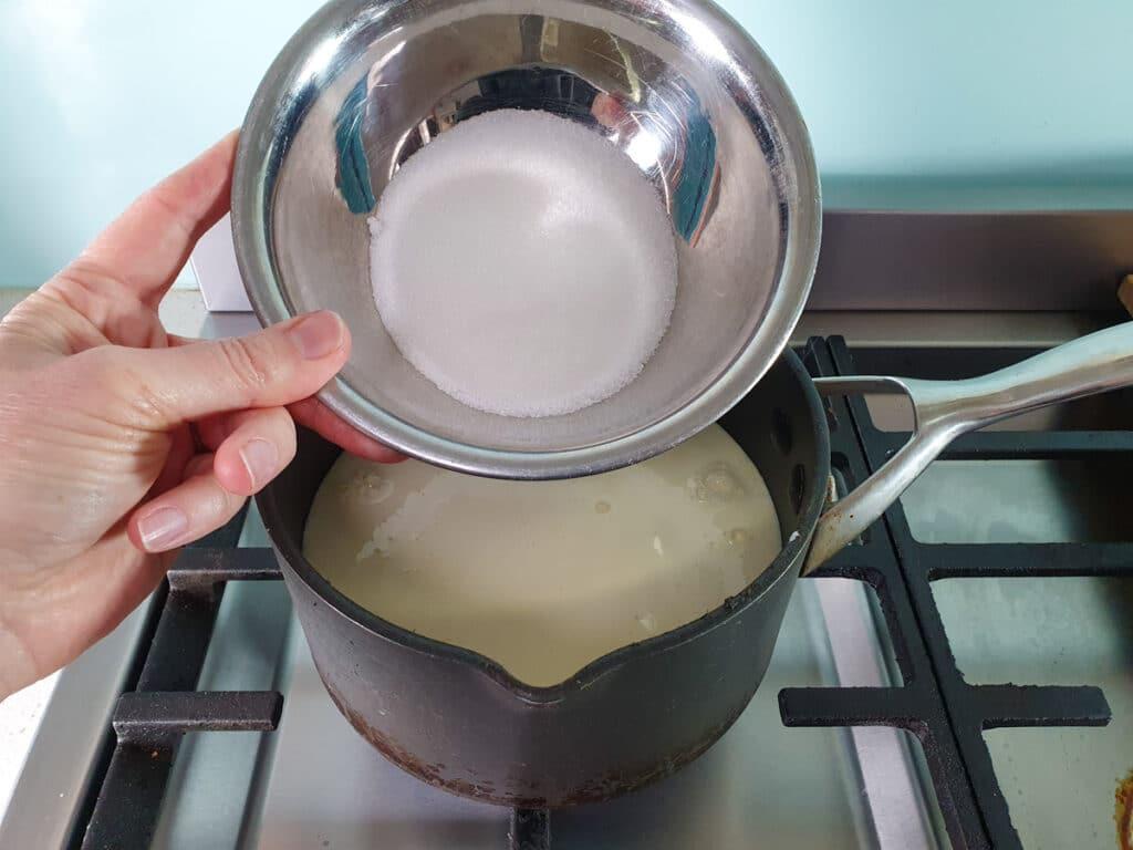 adding sugar to pot on stove.