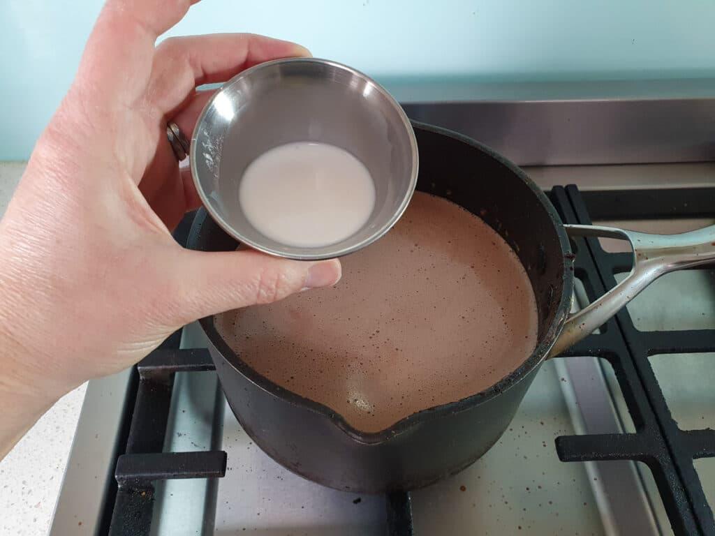 adding tapioca starch and milk slurry to pot on stove.