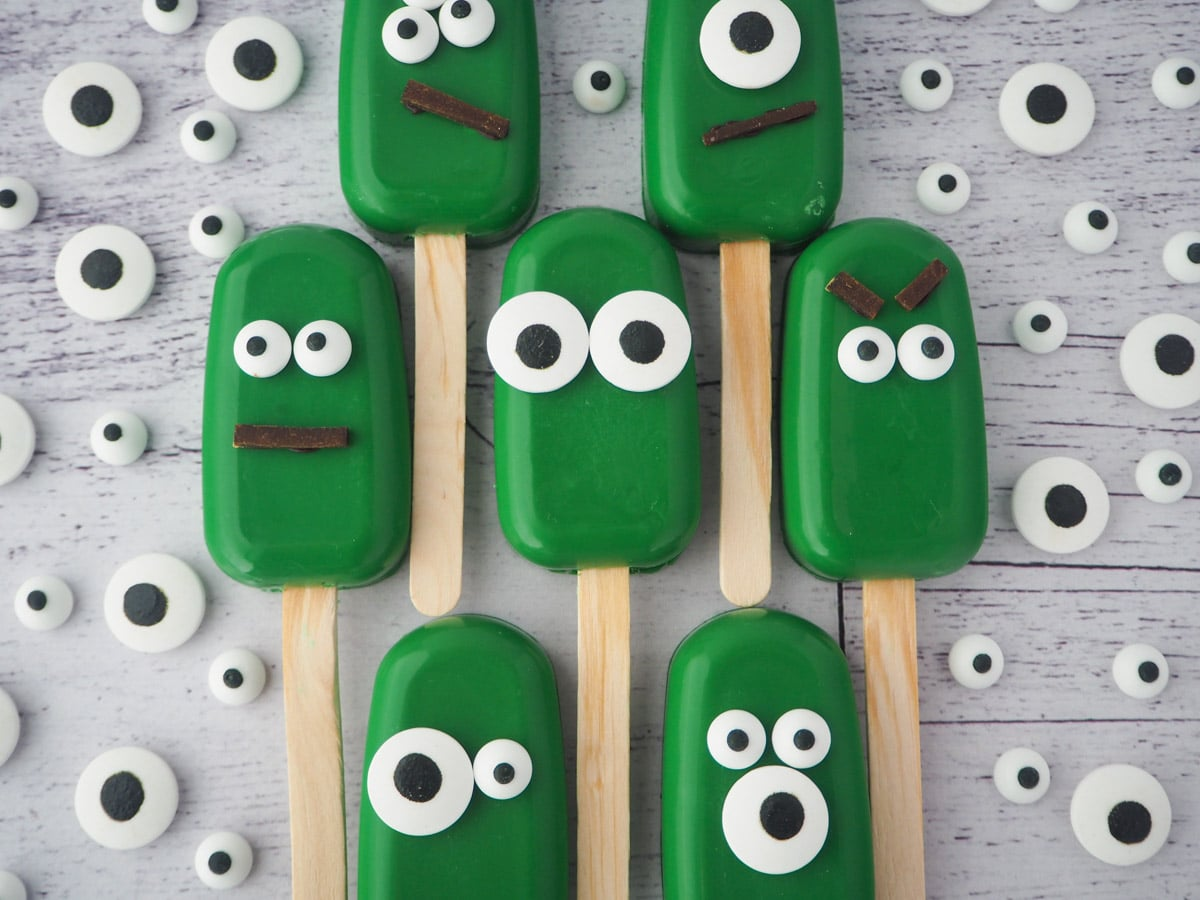 Row of six monster cakesicles, all different, surrounded by candy eyes.