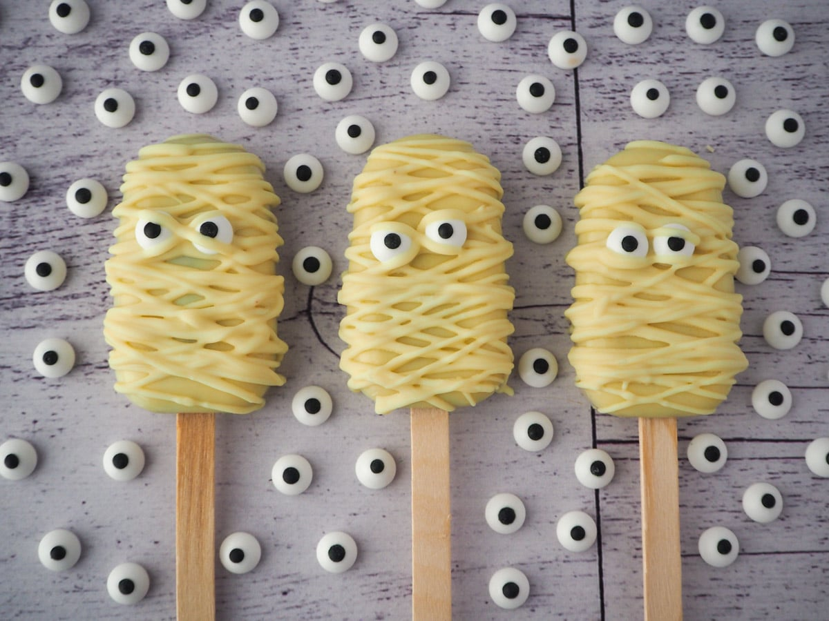 Row of three mummy cakesicles, surrounded by candy eyes.