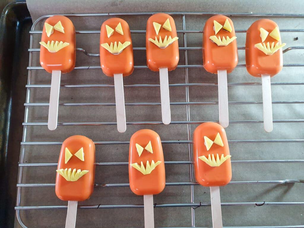 Sticking jack-o-lantern decorations onto cakesicles.