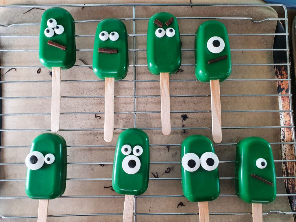 Sticking decorations onto monster cakesicles.
