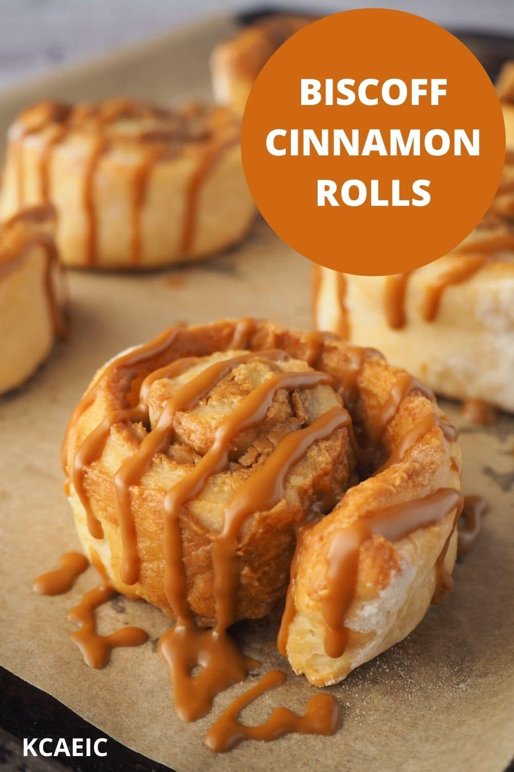 Biscoff roll drizzled with Biscoff on a baking tray, with text overlay, Biscoff Cinnamon Rolls, KCAEIC.