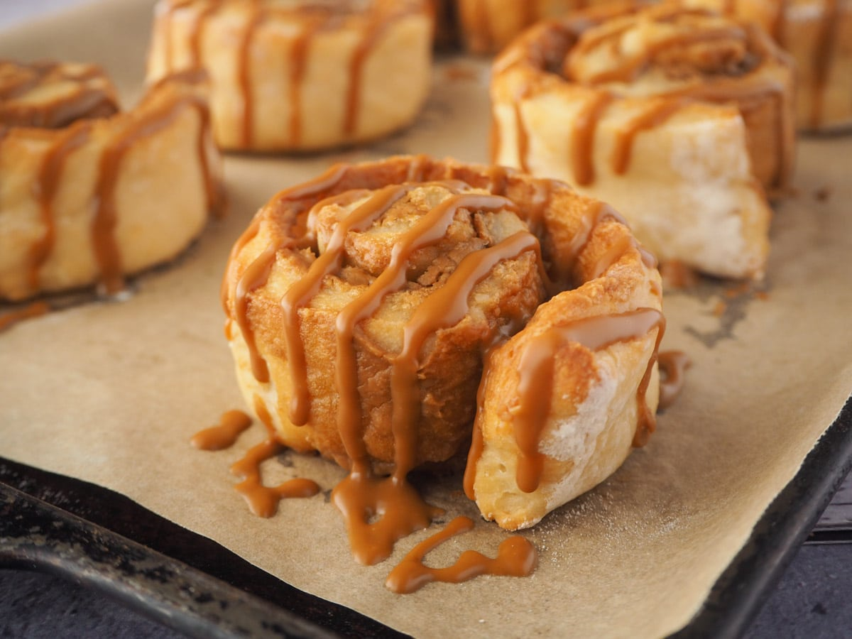 Biscoff roll drizzled with Biscoff on a baking tray.
