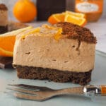 Close up Slice of cheesecake with fork, fresh oranges and dark chocolate in the background.