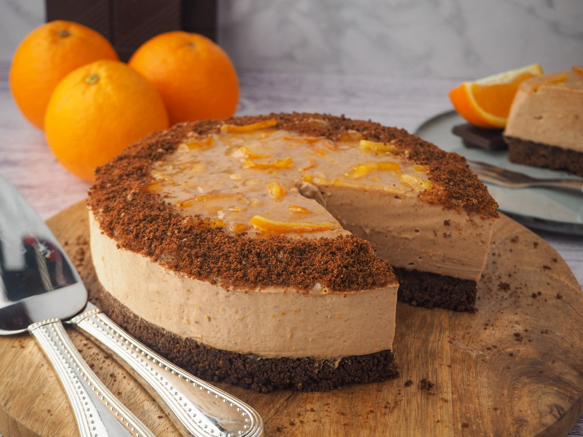 Serving cake, with silverware and slice of cake and fresh orange and chocolate in the background.