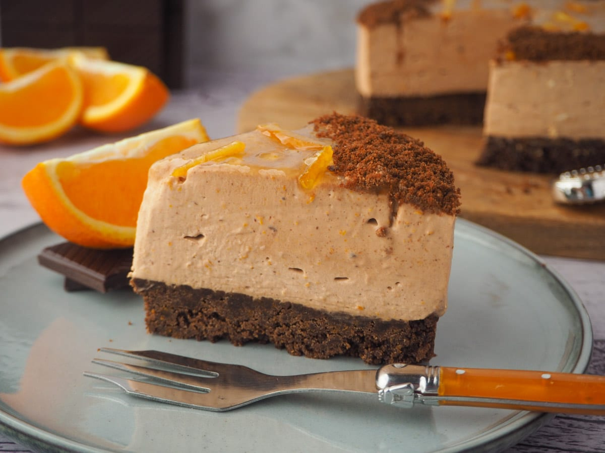 Slice of cheesecake with fork, rest of cake, fresh oranges and dark chocolate in the background.