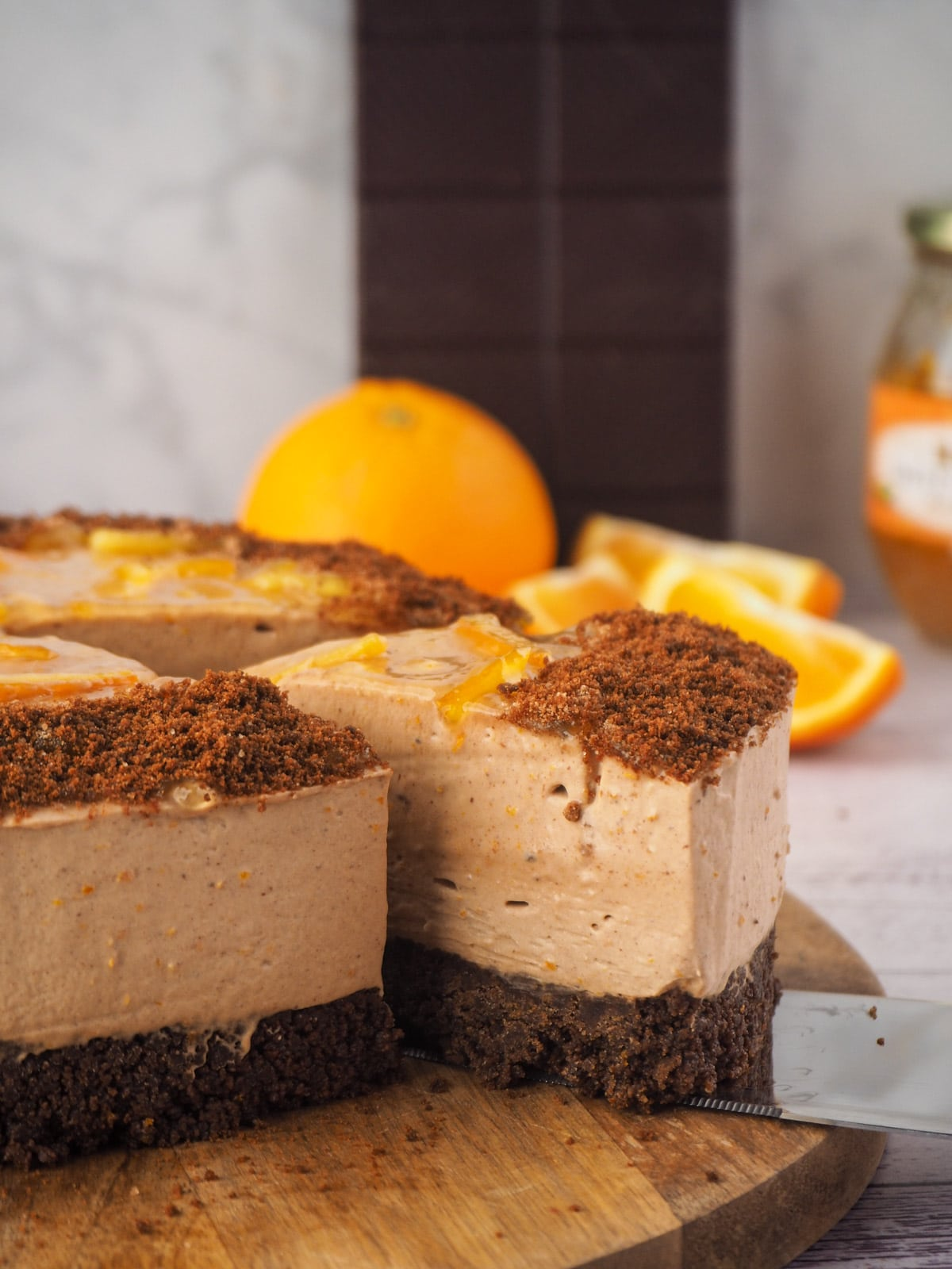 Serving a slice of cheesecake with fresh oranges and dark chocolate in the background.