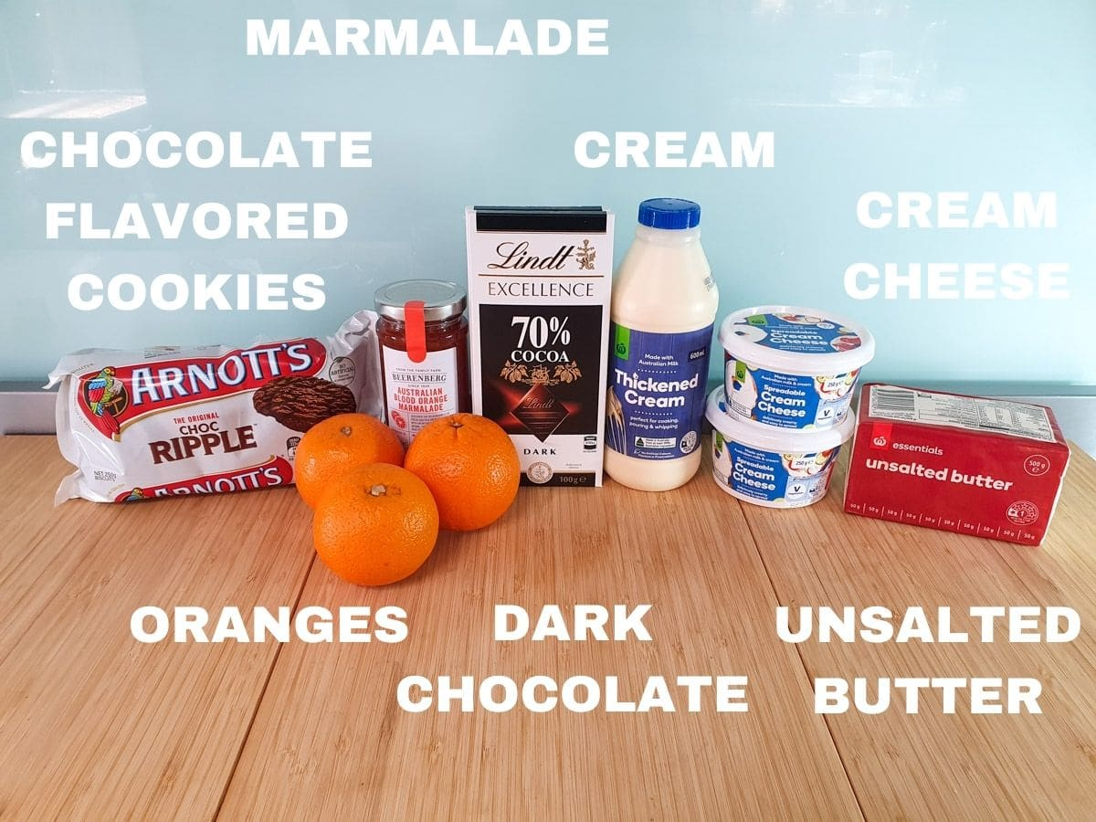 Ingredients, chocolate flavored cookies, five oranges (not three as pictured), orange marmalade, dark chocolate, thickened cream, full fat cream cheese, unsalted butter, white sugar (not pictured).