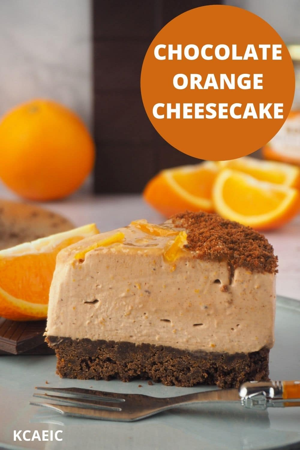 Slice of cheesecake with fork, fresh oranges and dark chocolate in the background and text overlay, chocolate orange cheesecake and KCAEIC.