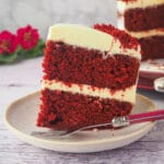 Close up slice of chocolate red velvet cake on a plate with fork and cake and flowers in the background.